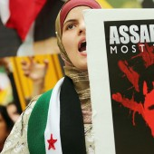 A protester holds an anti-Bashar Assad, President of Syria, sign